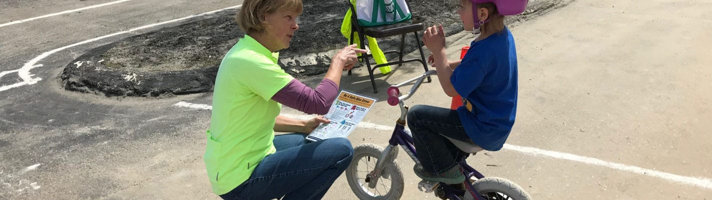 An instructor chats with a student at a bike rodeo