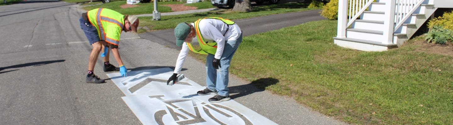 Twp people use stencil to paint bike sharrow on road image